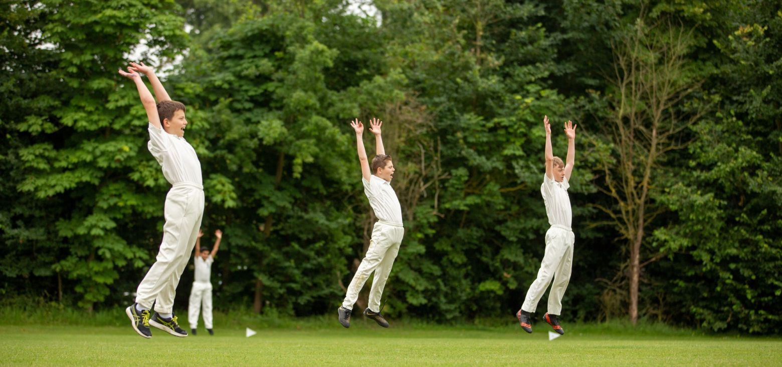young cricket players jumping in the air