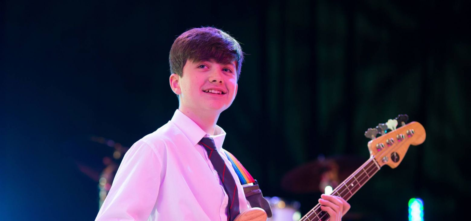 smiling school boy performing guitar