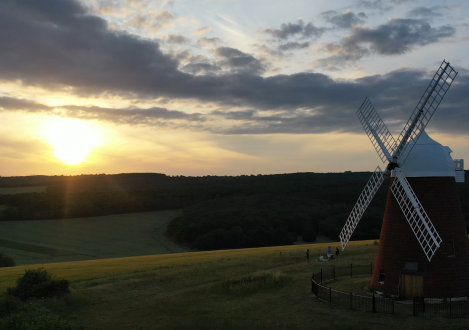 windmill in a field with the sun setting