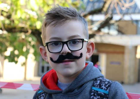young boy wearing glasses and a fake moustache