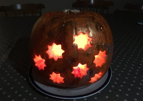A pumpkin carved with stars in the middle and lit up from the inside