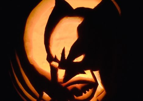 A pumpkin carving with Wolverine carved into the center