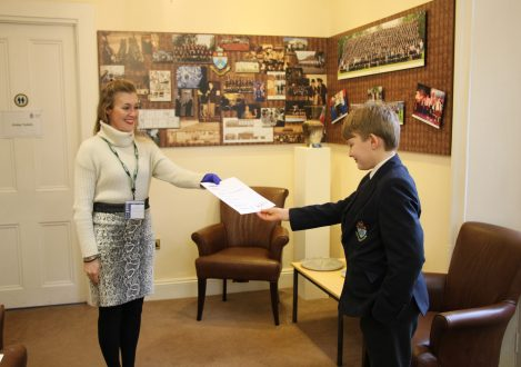Teacher handing school boy exam results