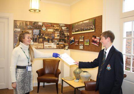 Teacher handing Halliford School student exam results