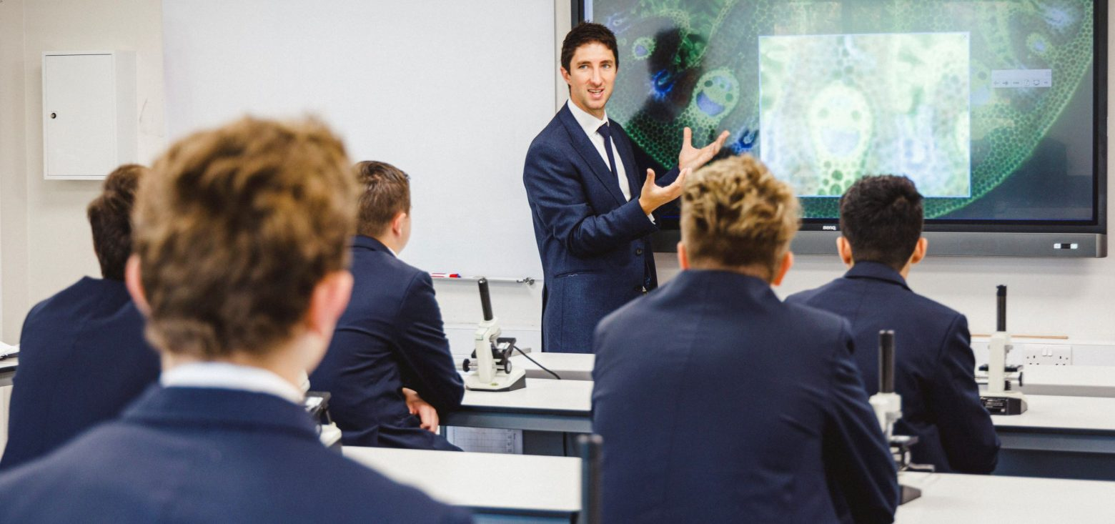 A teacher speaking to students in a Biology class. Students have microscopes on their desks