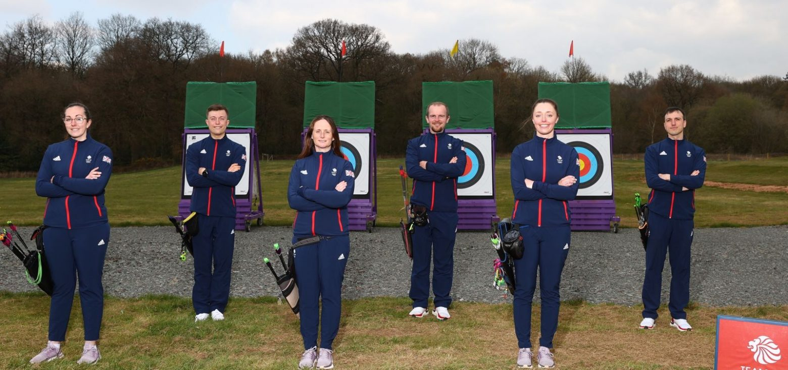 3 men and 3 women smiling behind archery targets ahead of the competition